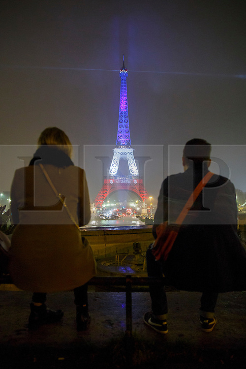 © Licensed to London News Pictures. 16/11/2015. Paris, France. The Eiffel Tower is illuminated in Red, White and Blue in honour of the victims of the Paris terror attacks in Paris, France on Monday, 16 November 2015. Photo credit: Tolga Akmen/LNP