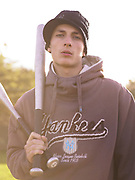 Young man holding two baseball bats.