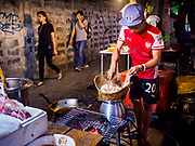 "24 MARCH 2017 - BANGKOK, THAILAND: People walk down the sidewalk as a worker prepares an order of ""sticky rice"" at a restaurant that is set up on the sidewalk of Sukhumvit Soi 55 (Thong Lo). The restaurant is being evicted from its location. Food cart vendors along Sukhumvit Road between Sois 55 (Thong Lo) and 69 (Phra Khanong) in Bangkok have been told by city officials that they have to leave the area by 17 April. It's a part of an effort by Bangkok city government, supported by the ruling junta, to take back the city's sidewalks. The evictions in the area are the latest in mass evictions of Bangkok street food vendors after similar actions elsewhere on Sukhumvit, in the Ari area, in Silom/Patpong and Ratchaprasong neighborhoods. The vendors in Thong Lo/Phra Khanong are popular with local office workers because most of the formal restaurants in the area serve foreign tourists and upper class Thais and are very expensive. The street food carts serve meals starting at about 35Baht ($1US). The city has not announced if they will provide alternative locations for the carts.     PHOTO BY JACK KURTZ"