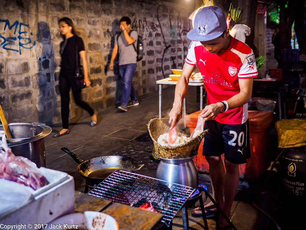 """24 MARCH 2017 - BANGKOK, THAILAND: People walk down the sidewalk as a worker prepares an order of """"sticky rice"""" at a restaurant that is set up on the sidewalk of Sukhumvit Soi 55 (Thong Lo). The restaurant is being evicted from its location. Food cart vendors along Sukhumvit Road between Sois 55 (Thong Lo) and 69 (Phra Khanong) in Bangkok have been told by city officials that they have to leave the area by 17 April. It's a part of an effort by Bangkok city government, supported by the ruling junta, to take back the city's sidewalks. The evictions in the area are the latest in mass evictions of Bangkok street food vendors after similar actions elsewhere on Sukhumvit, in the Ari area, in Silom/Patpong and Ratchaprasong neighborhoods. The vendors in Thong Lo/Phra Khanong are popular with local office workers because most of the formal restaurants in the area serve foreign tourists and upper class Thais and are very expensive. The street food carts serve meals starting at about 35Baht ($1US). The city has not announced if they will provide alternative locations for the carts.     PHOTO BY JACK KURTZ"""