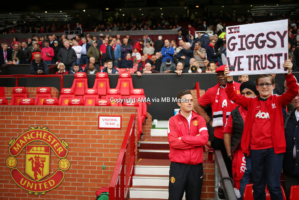 A fan of Manchester United holds up a banner saying IN GIGGSY WE TRUST