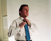 The stylish British Rt. Hon. Alan Milburn, MP for Darlington is seen in a studio setting in an official Government room loacted in the Cabinet Office, Whitehall, London, England. In shirtsleeves he adjusts his blue patterned tie. Milburn was a supporter of Tony Blair (and therefore called a Blairite) and held numerous governmental posts, including: Minister of State for Health (1997-1998); Chief Secretary to the Treasury (1998-1999); Secretary of State for Health (1999-2003) and Chancellor of the Duchy of Lancaster (2004 to 2005). Source: www.alanmilburn.co.uk.