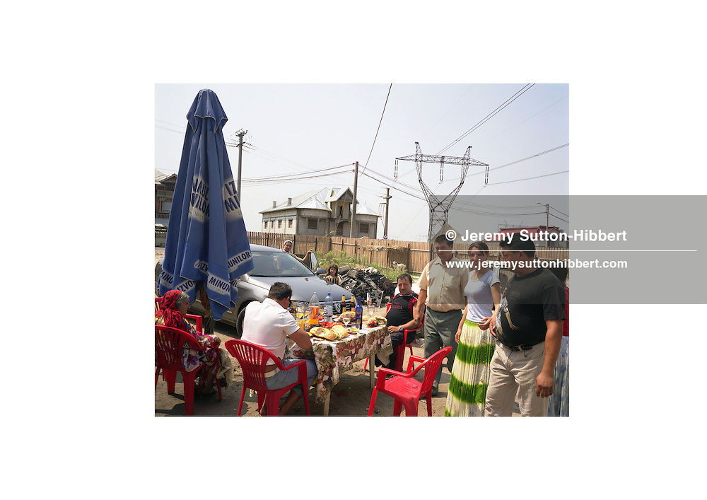 A Roma family hold a party in their yard, with food and drinks, to celebrate the arrival of their new 40,000 USD Volkswagen Passat car, in the village of Sintesti, in Romania, early August 2006. The Kalderari roma of Sintesti are by tradition metal workers, originally making alcohol stills, pots and pans, but now dealing in scrap metal. The large profits from their business have enabled them to build large houses in the village of Sintesti, 20km from Bucharest, and to invest in fast, Western brand name cars such as BMW's, Mercedes and Porsche.