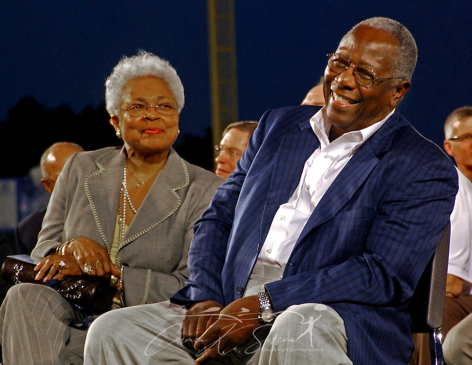 """Baseball legend Hank Aaron and his wife, Billye Aaron, smile as they listen to Hall of Famer Willie Mays reminisce during the dedication of the Hank Aaron Childhood Home and Museum April 14, 2010 at Hank Aaron Stadium in Mobile, Ala. Aaron's childhood home, originally built by his father, was moved to the stadium's """"Gaslight Park"""" and restored in November 2008. The celebration, which included a ribbon-cutting and private reception, was attended by a star-studded roster of Hall of Famers and baseball dignitaries, including Mays, Reggie Jackson, Ozzie Smith, Bob Feller, Rickey Henderson, and Bruce Setter, along with President of Minor League Baseball Pat O'Conner, President of the National Baseball Hall of Fame Jeff Idelson, MLB Commissioner Bud Selig, and Hall of Fame senior director of exhibitions Erik Strohl. (Apex Mediawire photo by Carmen K. Sisson)"""