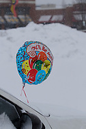 """This balloon, attached to a windshield wiper near the U.D. campus, says, """"You'll Be Missed!""""  It's most likely NOT referring to the snow that now covers the car, or the pile of snow in the parking lot.  Most drivers won't miss the snow a bit."""