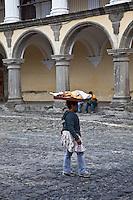 Local woman walking in the main square of Antigua with Palacio de los Capitanes Generale.