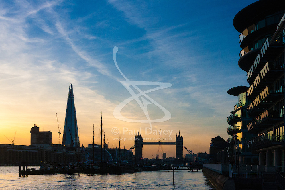 London, March 10th 2015. The sun sets over London after a warm early spring day. PICTURED: Dutch sailing barges tied up at Hermitage Moorings in Wapping in front of Tower Bridge, with The Shard in the background.