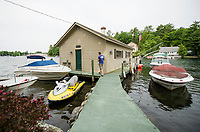 Surrounded by more modern vessels Kevin Buttermore of Hi Gloss Boat Restoration walks into a boathouse circa 1920 on Lake Winnipesaukee, New Hampshire. ©2018 Karen Bobotas Photographer