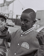 A kid strikes a fighting pose, Southall, UK, 1987.