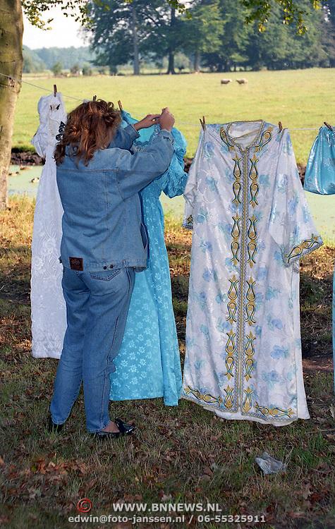 NLD/s'Graveland/19911120 - Marokkaanse kleding hangt aan een Nederlandse waslijn te drogen opghangen door een vrouw
