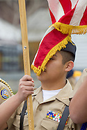 Middletown, New York - A member of the Middletown High School Naval Junior ROTC carries the American flag in the 60th annual Middletown Little League parade on April 14, 2013.
