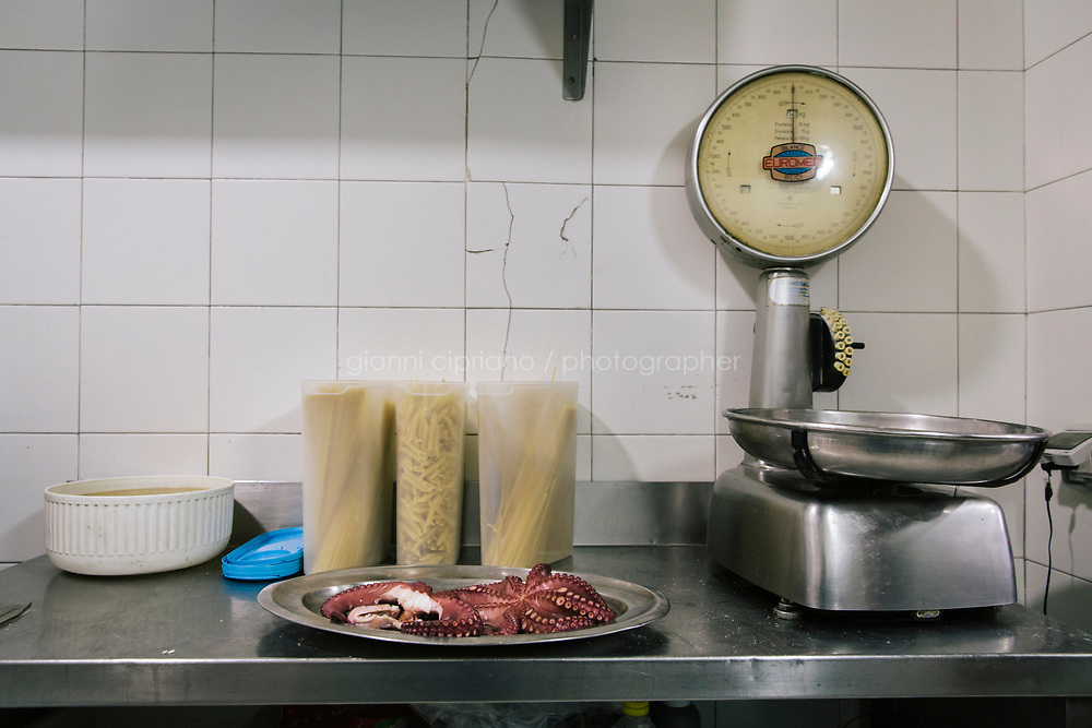 NAPLES, ITALY - 20 MARCH 2018: An octopus and pasta are seen here by a scale in the kitchen the Pizzeria e Trattoria Vigliena in Naples, Italy, on March 20th 2018.<br /> <br /> Pizzeria e Trattoria Vigliena is a restaurant outside of the city center and adjacent to the port. At lunch, the place is packed with workers from the docks and ship owners and workers from the recently built Marina Vigliena.<br /> <br /> The restaurant is owned by Raffaele Esposito, Concetta&rsquo;s son and the third generation of a family of chefs who founded this restaurant in the middle of the 20th century