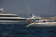 Luxury yachts line up along edge of race course to watch America's Cup fleet racing; Valencia, Spain.