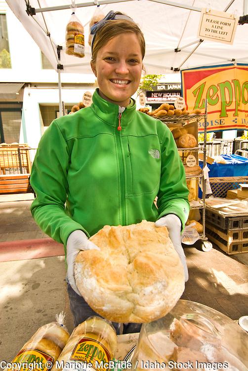 Woman selling fresh bread at Farmers Market in downtown, Boise, Idaho.  Model Release