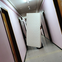 Macadonian man holding a mattress being moved to a new room in a centre for refugees  and asylum seekers run by the Hospice Generale.