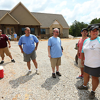 Renae Bennett, co-founder of the Itwamba Crossroads Ranch, points out the cabins under construction to her residents as they stand in front of their Central Lodge. All together there will be 15 cabins with 5 in the construction process.