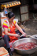 A vendor cleans fish on the street in Shanghai, China