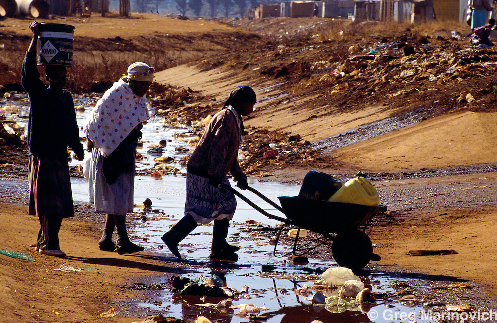 Bekkersdal, South Africa, 1995. Women push a barrow with water containers across a litter-strewn stream in Bekkersdal, West Rand, South Africa.
