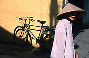 April 2002 - Hoi An, Vietnam - A woman wearing a conical hat. Photo Credit: Luke Duggleby