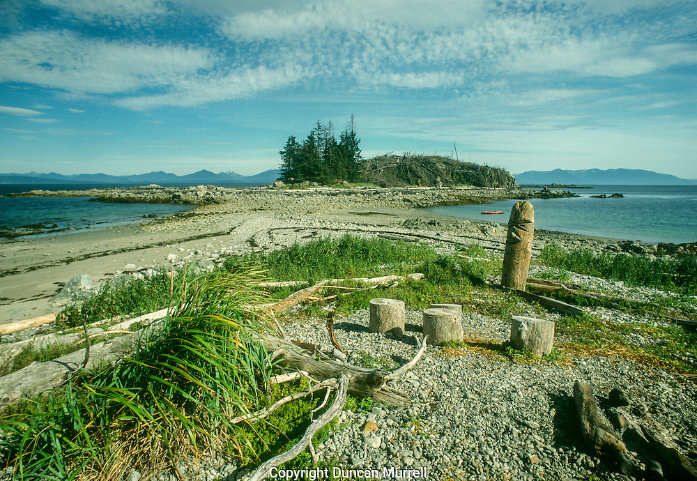 "This was one of my favourite campsites. It is directly opposite the native town of Angoon, where I often used to catch the ferry to from Petersburg to start my kayaking trips in the summer. I then usually had a relatively easy crossing to get here. To the right and south of the photo is Peril Strait, which is a narrow passage that leads to Sitka and the Pacific Ocean. Offshore is the submerged Morris Reef, which was one of the regular feeding places for bubble net feeding humpback whales, which were usually the ones that I dubbed ""the Famous Five"". The converging currents there create strong upwellings and choppy water that made the conditions difficult at times. It was a great campsite because it has a beaches facing north and south with a small causeway leading to a small islet that was cut-off at high tide. It made it easier for me to land  depending on which way the wind was blowing. The islet looks odd in this photo because half of the trees burnt down one summer. I was paddling across Chatham Strait and could see smoke belching from the islet that was such a special lookout point for me. As soon as I landed I found a big empty plastic oil drum on the beach and used it to go back and forth with water to make a fire break to save half the islet. But it was still upsetting for me when I was sitting next to my campfire in the evening watching one tree after another crashing down on the other side, sending up fireworks of glowing embers in the night sky. It was a really dry summer that year and small islands without any groundwater are particularly vulnerable to slow burning fires smouldering in the tinder-dry forest litter. In the foreground is a rudimentary totem and circle of log seats that some Tlingit native people from Angoon must have carved. I had been coming to this campsite for a few years, and was pleasantly surprised to find these here one summer, and they added more unique character to this campsite, as well as the islet with half its trees gone."