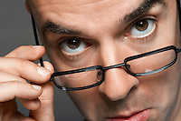 Balding man hand on glasses making a face close-up