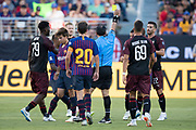 August 4, 2018; Santa Clara, CA, USA; Soccer referee Baldomero Toledo issues a yellow card to AC Milan midfielder Jose Mauri (4) after committing a foul against FC Barcelona midfielder Ricky Puig (8) during the second half in an International Champions Cup soccer match at Levi's Stadium. AC Milan defeated FC Barcelona 1-0.