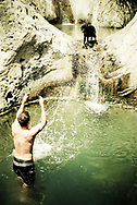 A man splashing water on his dog at a waterfall named Seven Falls in Santa Barbara, California.  (releasecode: jk_mr1028) (Model Released)