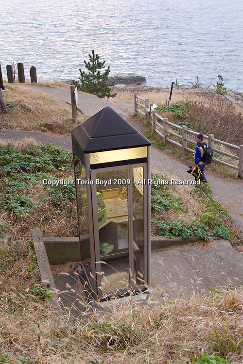 This is a special telephone booth installed close to to where many suicides occur along the rocky cliffs of Tojinbo, a popular tourist spot on the Japan Sea coast. This booth has a sign large sign with a number to call for help, as well as a donation box with ten yen coins and telephone cards for distressed individuals to use as a last resort to save themselves. Located in Sakai City, Fukui Prefecture, the scenic Tojinbo area known for it's coastal beauty, seafood and onsen hot springs resorts now adds suicide as a reason to come here. In 2008 twenty suicides occurred here, but this figure varies between Sakai City officials and a suicide help group dedicated to preventing suicides here, and also responsible for this special telephone booth. Called Kokoro ni Hibiku Bunshu Henshukyoku, this NPO founded in 2004 by retired policeman Yukio Shige, who along with a group of volunteers patrols the cliffs on a daily basis to deter those contemplating jumping to their deaths. According to Shige, age 65, in the past five years since he founded his NPO, he is responsible for talking 222 people out of killing themselves. But even with Shige's efforts, the deaths here continue and as of late November, 2009, the current number of annual suicides at Tojinbo stands at thirteen. Japan has one of the highest suicide rates in the world and 2009 may surpass the record 34,427 deaths that occurred here in 2003. This increase is though to be a result of the Japanese recession which has been worsened by the global economic downturn. Depression is the number one cause for suicide in Japan, followed by illness and debt. Photo taken November 27, 2009.