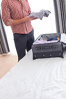 Midsection of young businessman taking shirt from suitcase in hotel room