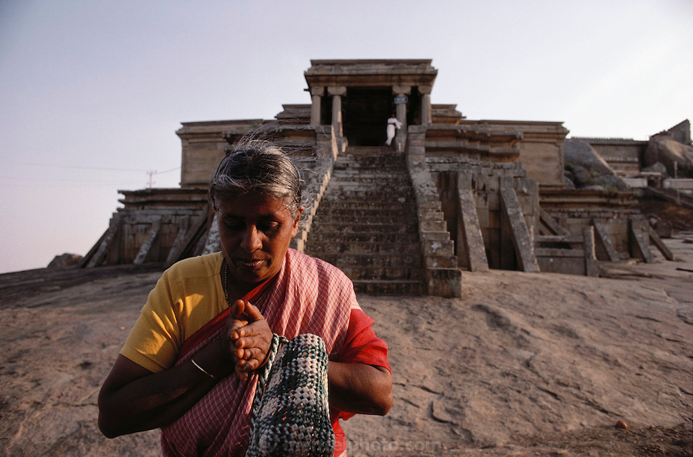 A woman in front of the sacred Jain site of Sravanbelgola, 93km north of Mysore, consists of two hills and a large Tank. On one of the hills, Indragiri (also known as Vindhyagiri), stands an extraordinary eighteen meter high monolithic statue of a naked male figure, Gomateshvara, which is the largest freestanding sculpture in India. The name of the other hill is Chandragiri, marking the arrival of Jainism in southern India..