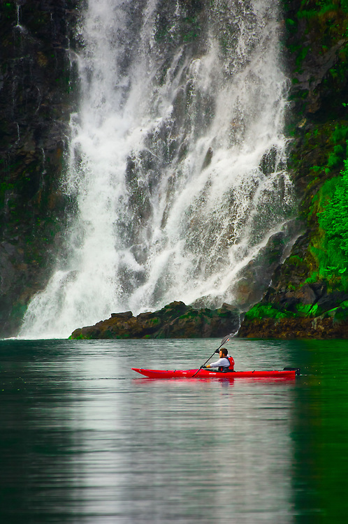 Man sea kayaking in front of Red Bluff Bay Falls, Red Bluff Bay, Inside Passage, Southeast Alaska