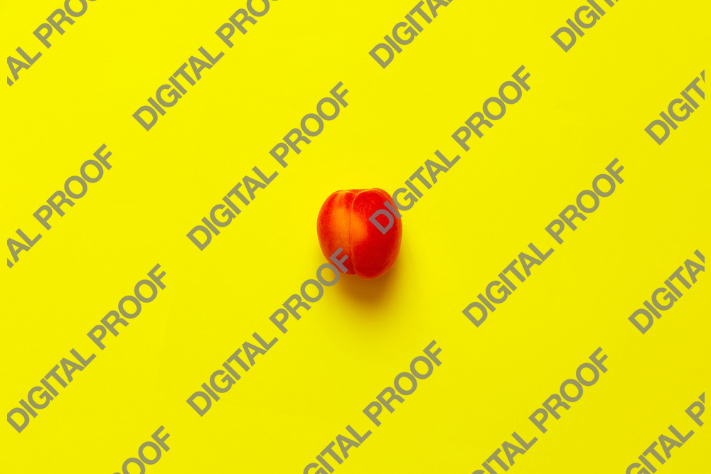 Lonely Apricot  isolated over a yellow background viewed from above, flatlay style
