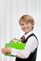 Portrait of a cheerful young birthday boy with gift