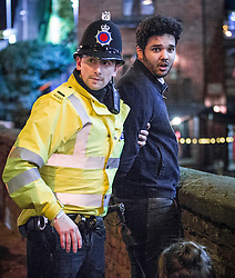 "© Licensed to London News Pictures . 19/12/2015 . Manchester , UK . A police officer detains a man after another man is punched , at Deansgate Locks . Revellers in Manchester enjoy "" Mad Friday "" - also known as "" Black Eye Friday "" - the day on which emergency services in Britain are typically at their busiest , as people head out for parties and drinks to celebrate Christmas . Photo credit : Joel Goodman/LNP"