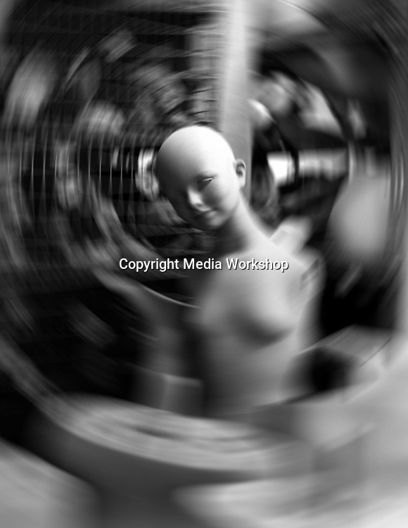 Store window dummy or mannequin with other parts in factory; spinning blur creates surreal vertigo effect.