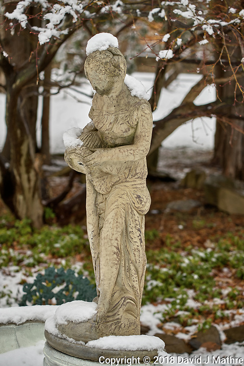 Birdbath statue with snow in April -- Winter is not gone. Image taken with a Leica TL2  camera and 60 mm f/2.8 lens (ISO 100, 60 mm, f/3.5, 1/160 sec).