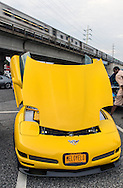 Bellmore, New York, USA. 12th June 2015. A modified yellow 2003 Corvette 50th Anniversary model, with Lamborghini doors (AKA vertical scissors doors and Lambo doors) and chrome trim added to inside of hood to reflect engine, an award winning car owned by Grey Cherveny of Bay Shore, is displayed  at the Friday Night Car Show held at the Bellmore Long Island Railroad Station Parking Lot, with LIRR train passing on overhead track platform, Hundreds of classic, antique, and custom cars were on view at the free weekly show, sponsored by the Chamber of Commerce of the Bellmores.