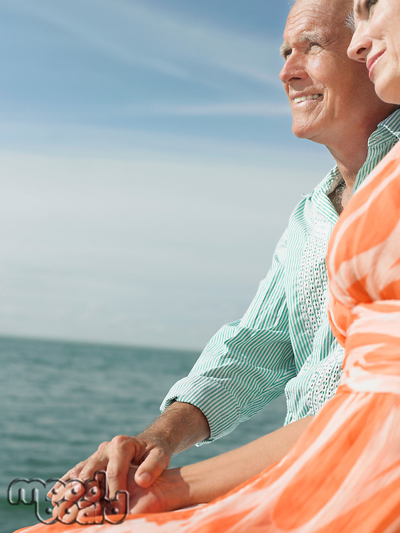 Couple sitting on edge of pier looking at view side view