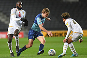 Wycombe Wanderers striker Alex Samuel (25) dribbles between Milton Keynes Dons midfielder Hiram Boateng (26) and Milton Keynes Dons defender Matthew Sorinola (40) during the EFL Trophy match between Milton Keynes Dons and Wycombe Wanderers at stadium:mk, Milton Keynes, England on 12 November 2019.