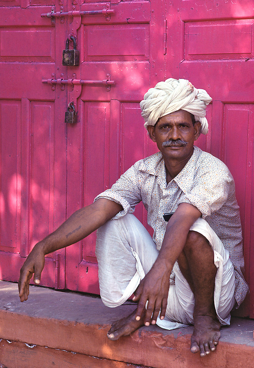 A turbaned man waits by pink door in Jaipur, Rajasthan, India.