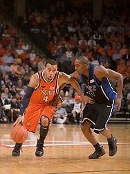 Virginia guard Calvin Baker (4) dribbles past Duke guard DeMarcus Nelson (21).  The Virginia Cavaliers men's basketball team fell to the #6 Duke Blue Devils 86-70 at the University of Virginia's John Paul Jones Arena in Charlottesville, VA on March 5, 2008.