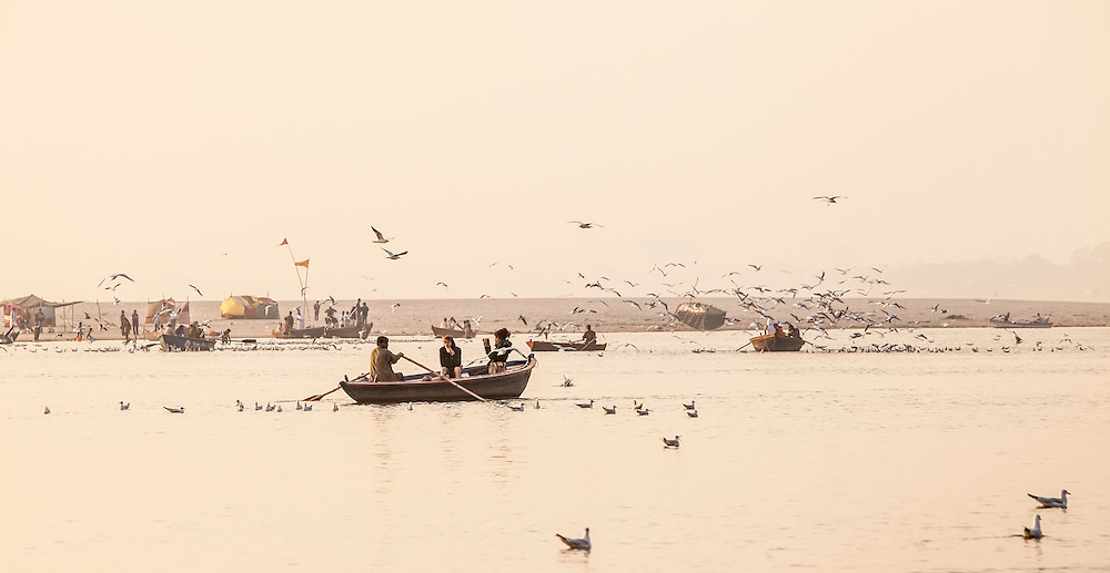 Tour boats on the Ganges river in Varanasi, India at sunrise.