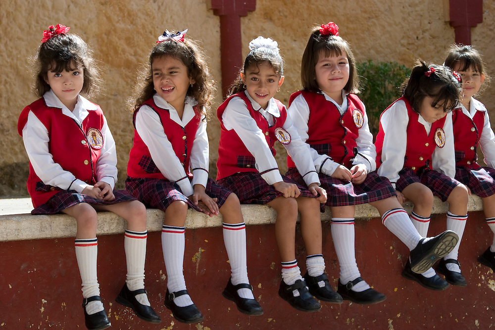 North America, Mexico, Yucatan, Valladolid, girls in school uniforms sitting on wall