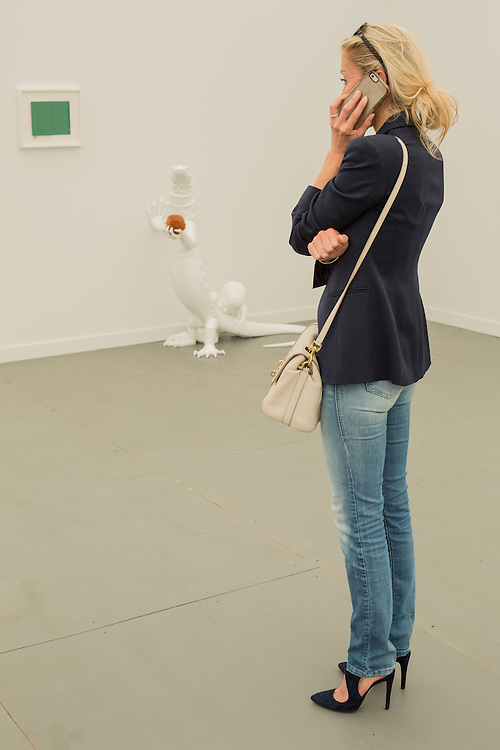 """A woman chats on her phone in the gallery of Zeno X, from Antwerp. The white sculpture by Pietro Roccasalva is """"Fanfaro"""", made of painted wood and a fried rice ball."""