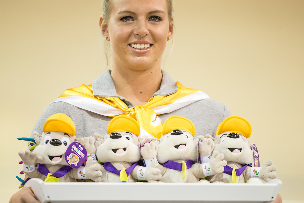 A medal bearer stands with her tray of medals and Pachi dolls (the games mascot) during the medal ceremony for the women's cycling team pursuit at the 2015 Pan American Games in Toronto, Canada, July 17,  2015.  AFP PHOTO/GEOFF ROBINS