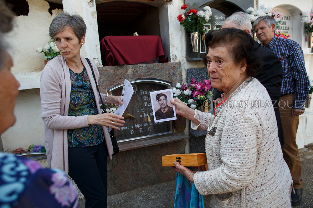 19/05/2018. Carmen Benito Alcantarilla (R) holds a picture of his uncle Valentin Alcantarilla Mercado who was assassinated by dictator Francisco Franco's forces as his remains are placed inside a niche during his burial at the cemetery on May 19, 2018 in Sacedon, Guadalajara province, Spain. General Franco's forces killed Timoteo Mendieta and other people between 1939 and 1940 after Spain's Civil War and buried them in mass graves in Guadalajara's cemetery. Argentinian judge Maria Servini used the international human rights law and ordered the exhumation and investigation of Mendieta's mass grave. The exhumation was carried out by Association for the Recovery of Historical Memory (ARMH) recovering 50 bodies from 2 mass graves and identified 24 of them. Spain's Civil War took the lives of thousands of people on both sides, but Franco continued his executions after the war has finished. Spanish governments has never done anything to help the victims of the Civil War and Franco's dictatorship while there are still thousands of people missing in mass graves around the country. (© Pablo Blazquez)