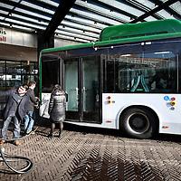 Nederland, Amsterdam , 6 februari 2013..Red Amsterdam organiseerde een demonstratie van diverse elektrische bussen op het voorplein bij de hoofdingang van het stadhuis.?Onder ruime belangstelling van de pers werden aan leden van de gemeenteraad en wethouder Eric Wiebes diverse elektrische bussen gepresenteerd en was er de mogelijkheid om een proefrit te maken..Volgens verkeerswethouder Eric Wiebes is de stand der techniek nog niet zover dat er binnenkort op grote schaal elektrische bussen kunnen worden ingezet. Bovendien zou het te kort dag zijn om een solide uitvraag naar elektrische bussen in de markt te zetten, waarmee in 2015 overgegaan zou kunnen worden op elektrisch rijden..Op de foto: Vertegenwoordigers van het Chinese merk BYD koppelen de stroom van de oplader af om vervolgens een ritje te gaan maken..Foto:Jean-Pierre Jans
