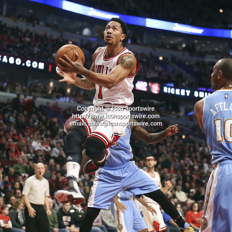 Jan. 1, 2015 - Chicago, IL, USA - Chicago Bulls guard Derrick Rose (1) goes for a reverse layup in front of Denver Nuggets guard Ty Lawson during the first half of their game on Thursday, Jan. 1, 2015 at the United Center in Chicago. The Bulls won 106-101