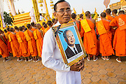 "01 FEBRUARY 2013 - PHNOM PENH, CAMBODIA:  A man walks along Sisowath Quay, Phnom Penh's riverfront boulevard, with a photo of former King Norodom Sihanouk during Sihanouk's funeral procession.  Norodom Sihanouk (31 October 1922 - 15 October 2012) was the King of Cambodia from 1941 to 1955 and again from 1993 to 2004. He was the effective ruler of Cambodia from 1953 to 1970. After his second abdication in 2004, he was given the honorific of ""The King-Father of Cambodia."" Sihanouk died in Beijing, China, where he was receiving medical care, on Oct. 15, 2012. His cremation is will be on Feb. 4, 2013. Over a million people are expected to attend the service.   PHOTO BY JACK KURTZ"