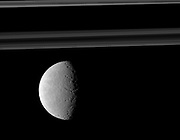 Rhea's trailing hemisphere shows off its wispy terrain on the left of this image which includes Saturn's rings in the distance. Cassini.